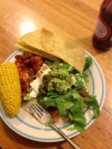 Dinner plate with chilli beans, salad, corn, taco chips, guacamole and soy sour cream...and a stubby of beer.